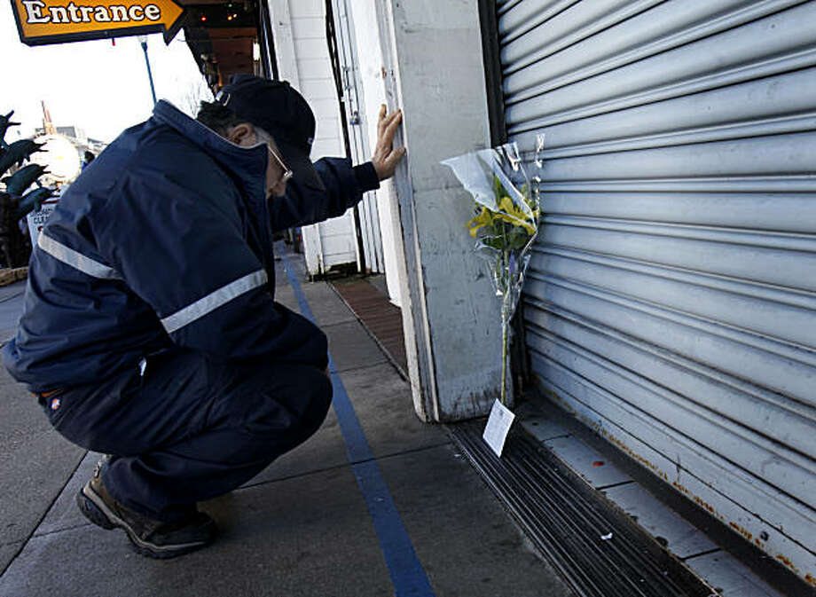 Mih Rasavong, who knew the victims, kneels and prays at the site of their storefront at San Francisco's Fisherman's Wharf on Tuesday. Photo: Brant Ward, The Chronicle