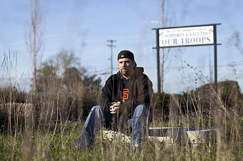 Jeremy Profitt, a veteran of the wars in Iraq and Afghanistan, sits by a sign showing support for the troops that his parents worked to get placed outside City Hall in his hometown of American Canyon, Calif., on Sunday, January 9, 2011.  Profitt wrote a piece about coming home from war that was placed on Another Source, an online cyber journal which allows former military personnel a chance to write first person narratives about their experiences. Photo: Laura Morton, Special To The Chronicle
