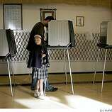 Olivian Georgenton, 7 years old, waits for her father Bill Georgenton as he votes at Goju Ryo Karate Center in San Francisco, Calif.