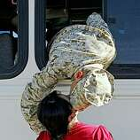 US Marine, Miguel Alvarez, drops out of a bus window to kiss his girlfriend Julia Rodriguez goodbye as  Marines take off from Twentynine Palms Marine Base, to begin their deployment to Iraq. They live in La Habra, Calif. It's Alvarez's first trip to Iraq.