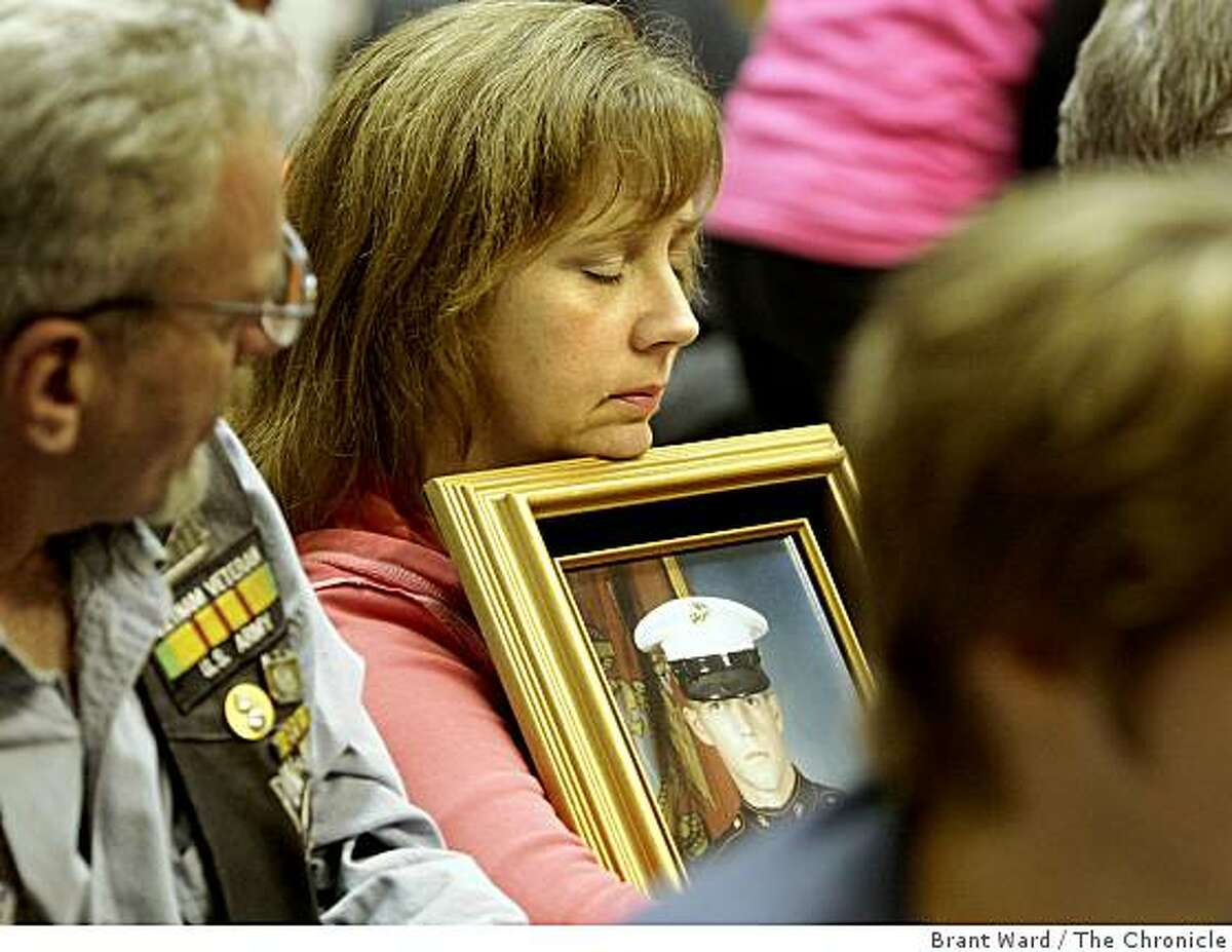 Deborah Johns held a portrait of her son, Sgt. William Johns, who is serving in Iraq. The Berkeley City Council didn't get to the proposal until late into the evening. Meanwhile members of the audience waited for the Marine's proposal to come up.