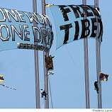 After three demonstrators unfurl banners in protest of China's crackdown in Tibet after scaling the south tower of the Golden Gate Bridge this morning a bridge worker cut the banner (top center) on April 7, 2008.4/7/08Photo by Frederic Larson / San Francisco Chronicle