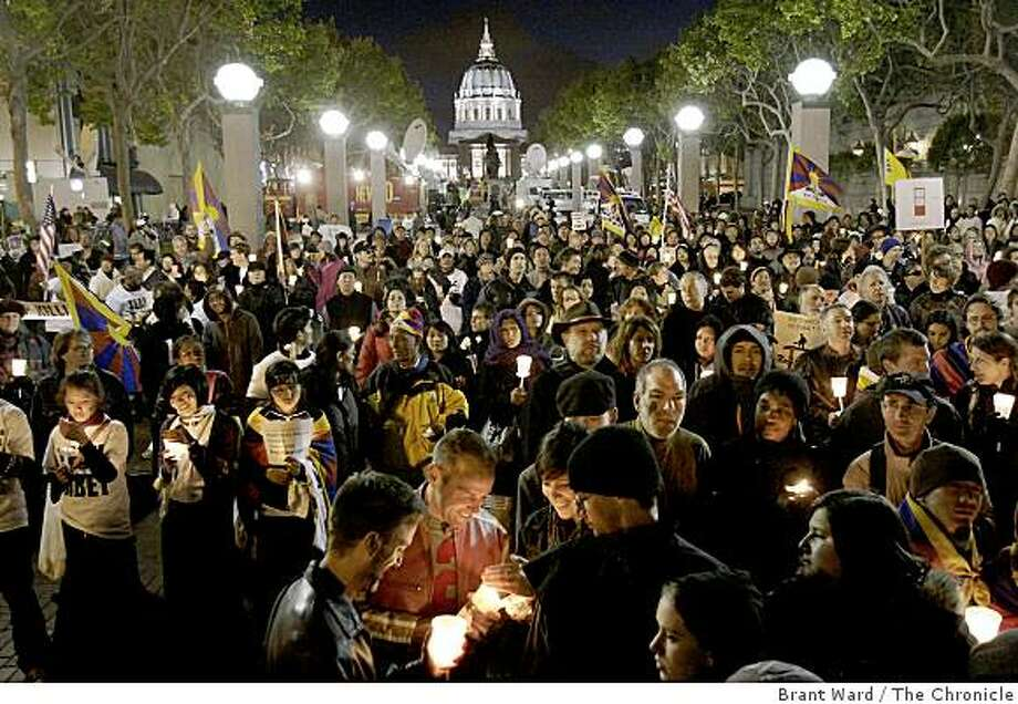 Even before the speakers were finished, the crowd lit their candles near the glow of San Francisco City Hall. Hundreds of Tibet supporters including actor Richard Gere and Archbishop Desmond Tutu took part in a candle light vigil near United Nations Plaza in San Francisco Tuesday, April 8, 2008. Photo: Brant Ward, The Chronicle