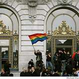 Dozens wait for the front doors of City Hall to open so the same-sex marriage ceremonies can begin, bob Slodervick of San Francsico, Calif. waves a rainbow flag to greet the visitors.