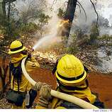 Firefighters Talon Sutherland, left, and Kody Dribnak hose down flames advancing towards a home in Concow, Calif., on Wednesday, July 9, 2008.