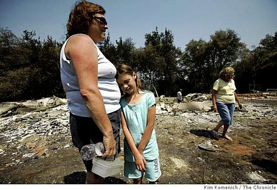 Laura Adams, 8, leans on her mother Tracy Adams on Saturday June 14, 2008 as the family visits their Paradise, Calif., home, which was destroyed my the Humboldt fire on Thursday. Laura's grandmother Grace Treadway walks in the background, right. A contingent of nearly 3,000 firefighters began to contain the Humboldt fire near Paradise, Calif. on Saturday. Photo: Kim Komenich, The Chronicle
