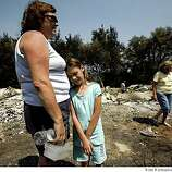 Laura Adams, 8, leans on her mother Tracy Adams on Saturday June 14, 2008 as the family visits their Paradise, Calif., home, which was destroyed my the Humboldt fire on Thursday. Laura's grandmother Grace Treadway walks in the background, right. A contingent of nearly 3,000 firefighters began to contain the Humboldt fire near Paradise, Calif. on Saturday.
