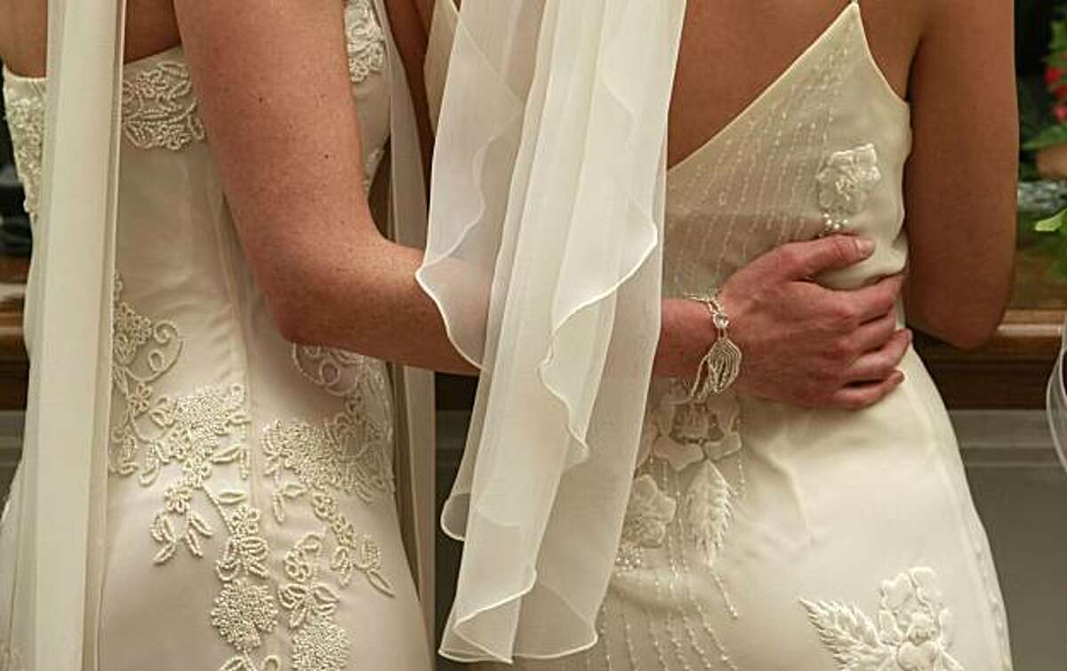 Wedding dresses in order for couple Amber Weiss and Sharon Papo as they wait in line for paperwork to complete their marriage certificate at San Francsico City Hall on June 17, 2008.