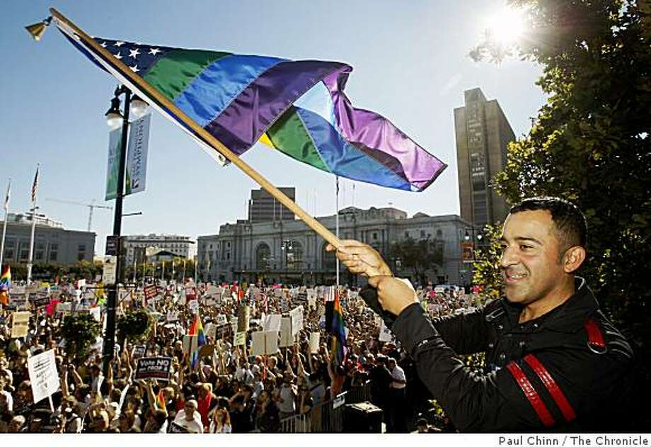 Alexander Sanchez waves a stars and rainbow stripes flag in front of thousands attending a rally at City Hall to protest the passage of the Proposition 8 marriage initiative in San Francisco, Calif., on Saturday, Nov. 15, 2008. Photo: Paul Chinn, The Chronicle