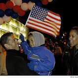 Joseph Smylie,6, in the arms of his dad Troy and his mom TJ, waving a flag at a block party at Jack London Square in  Oakland photographed  on Tuesday, November 4, 2008.