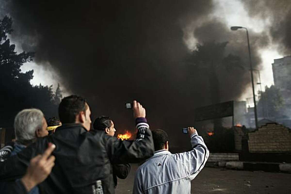 TOPSHOTS Egyptians take pictures with their cellphones of a burning police station set ablaze by rioters near the Sultan Hassan al-Rifai mosque in central Cairo on January 28, 2011. TOPSHOTS /