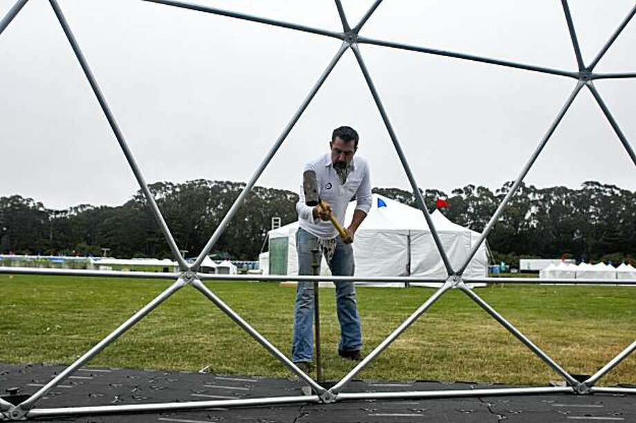 Rufus Bonham secures the posts for the bar garden tent for the Outside Lands festival at Golden Gate Park in the Polo Field, Wednesday August 26, 2009, in San Francisco, Calif. The weekend festival is the biggest of the year in San Francisco with over 90 bands. Photo: Lacy Atkins, The Chronicle