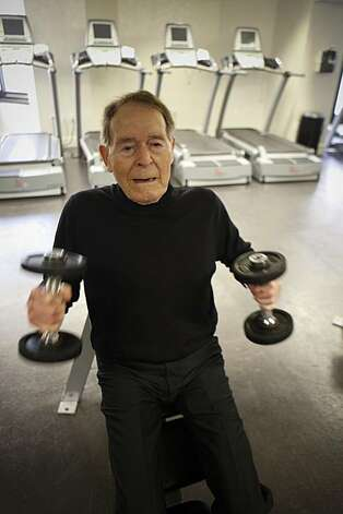 Fitness pioneer Jack LaLanne takes reporter Carolyn Zinko through a mini-workout at the Parc 55 Hotel in San Francisco in 2009. Photo: Russell Yip, The Chronicle