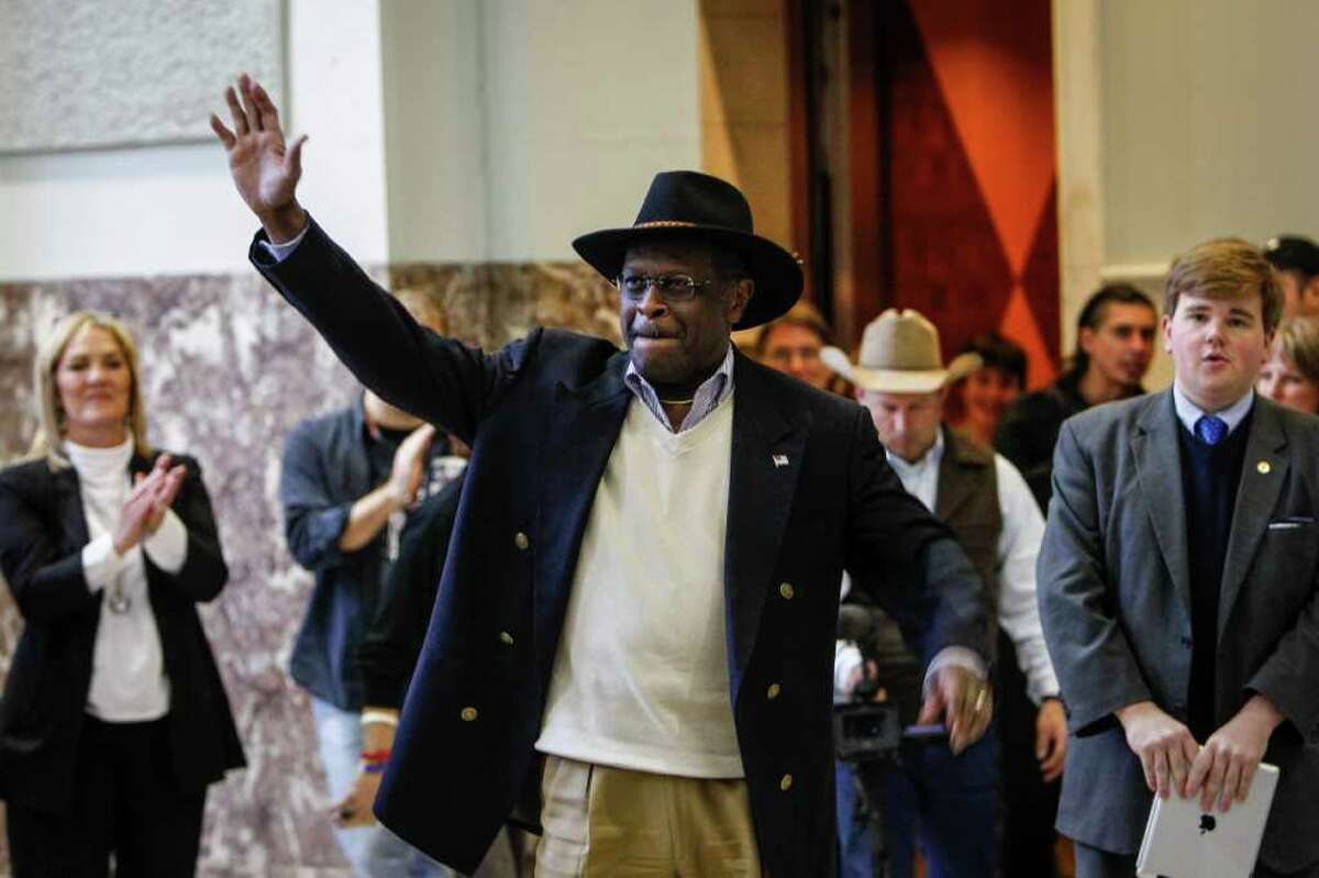 Past Presidential Candidate Herman Cain waves to the crowd as he arrives for the Saddle Up Texas Straw Poll event at Union Station at Minute Maid Park. Cain, a successful businessman, former radio shot host and creator of