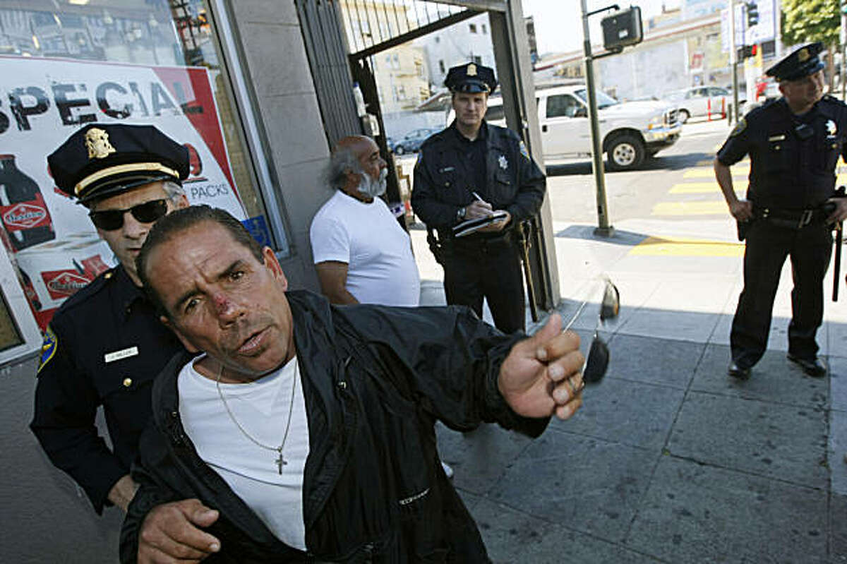 San Francisco Police Lt. Jim Miller (left) moves Shawn Nunez away who is upset that officer Steve Keith is citing Robert Lopez for drinking in public outside Valencia Grocery and Deli during the nightly foot beat in the Mission District Tuesday July 14, 2009.