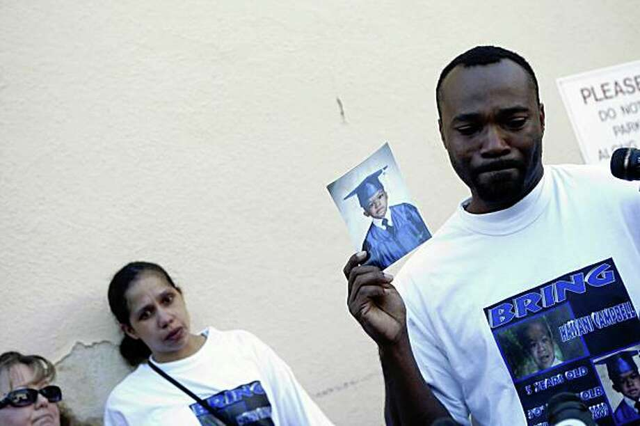 Louis Ross (right), foster father of missing 5-year-old Hasanni Campbell, holds a photograph of Hasanni while addressing the media while Jennifer Campbell (second from left), foster mother and aunt of 5-year-old Hasanni Campbell, listens during a vigil in back of the store where he was supposedly last seen, Shuz of Rockridge. in Oakland, Calif. on Monday, August 17, 2009. Photo: Lea Suzuki, The Chronicle