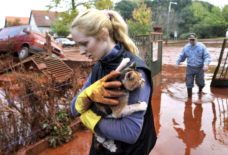 Tunde Erdelyi, left, saves her cat while Janos Kis, right, walks into their yard flooded by toxic mud in the town of Devecser, Hungary, Tuesday, Oct. 5, 2010. Monday's flooding was caused by the rupture of a red sludge reservoir at an alumina plant in western Hungary and has affected seven towns near the Ajkai Timfoldgyar plant in the town of Ajka, 100 miles (160 kilometers) southwest of Budapest. Photo: Bela Szandelszky, AP