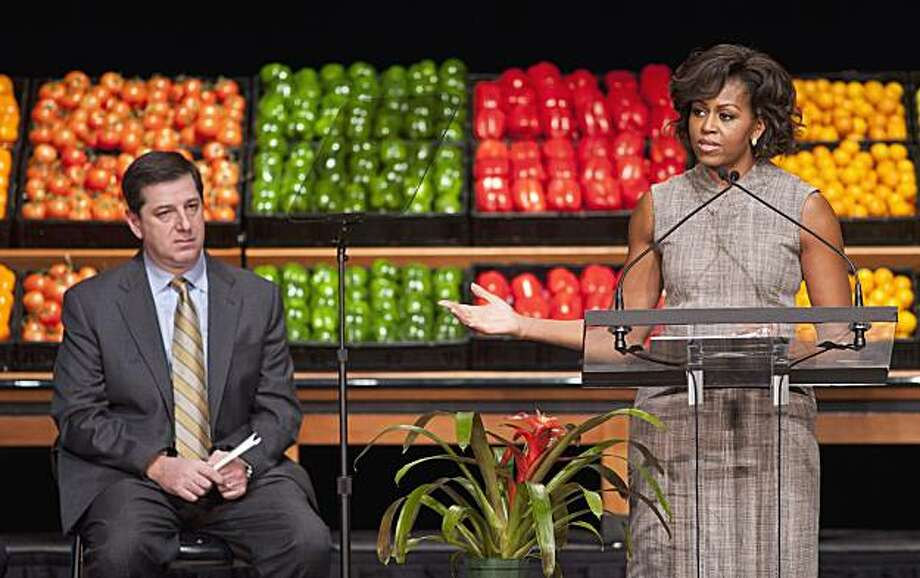 Wal-Mart President and CEO Bill Simon looks on as First lady Michelle Obama takes part in Wal-Mart's announcement of a comprehensive effort to provide healthier and more affordable food choices to their customers, Thursday, Jan. 20, 2011, in Washington. Photo: Cliff Owen, AP