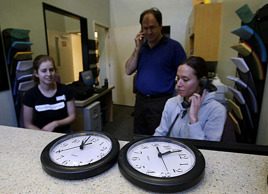 Wall clocks wait to be mounted while in the background, reproductive health specialists Carly Hann (left), Jacqueline Burgoyne (right) and technician Mark Stowe work on the telecom system for the opening of the new Planned Parenthood health clinic in San Francisco, Calif., on Tuesday, Jan. 18, 2011. Photo: Paul Chinn, The Chronicle