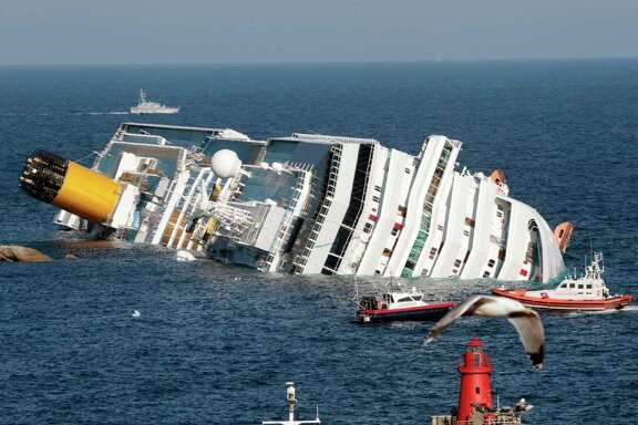 The luxury cruise ship Costa Concordia lays on its side after running aground the tiny Tuscan island of Giglio, Italy, Saturday, Jan. 14, 2012. A luxury cruise ship ran aground off the coast of Tuscany, sending water pouring in through a 160-foot (50-meter) gash in the hull and forcing the evacuation of some 4,200 people from the listing vessel early Saturday, the Italian coast guard said. (AP Photo/Gregorio Borgia)