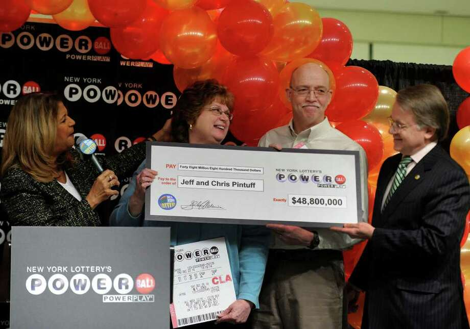 NYS Lottery's Yolanda Vega present Christine and Jeff Pintuff of Wilton as they show off their winning ticket as they received the winner's check of $48.8 million in the December 25th 2010 Powerball drawing from NYS Lottery Director Gordon Medenica(r) at a press event at the Empire Plaza in Albany February 11, 2011.   (Skip Dickstein / Times Union) Photo: SKIP DICKSTEIN / 2008