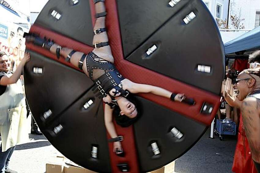 A young woman seems to enjoy her turn on the torture wheel at the Folsom Street Fair, a world-famous celebration of fetish, leather and S&M, on Sunday in San Francisco.