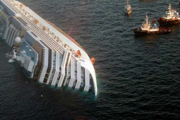 In this photo released by the Guardia di Finanza (border Police), the luxury cruise ship Costa Concordia leans on its side after running aground off the tiny Tuscan island of Giglio, Italy, Saturday, Jan. 14, 2012.  The luxury cruise ship ran aground off the coast of Tuscany, sending water pouring in through a 160-foot (50-meter) gash in the hull and forcing the evacuation of some 4,200 people from the listing vessel early Saturday, the Italian coast guard said.  The number of dead and injured is not yet confirmed Coast Guard Cmdr. Francesco Paolillo said. (AP Photo/Guardia di Finanza, ho)