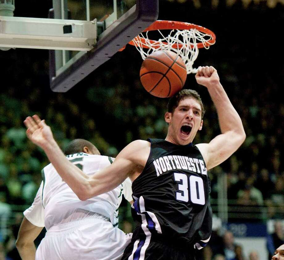 Northwestern forward Davide Curletti, right, reacts after dunking on Michigan State center Adreian Payne during the second half of a college basketball game on Saturday, Jan 14, 2012 in Evanston, Ill. Northwestern won 81-74.  (AP Photo/Brian Kersey)