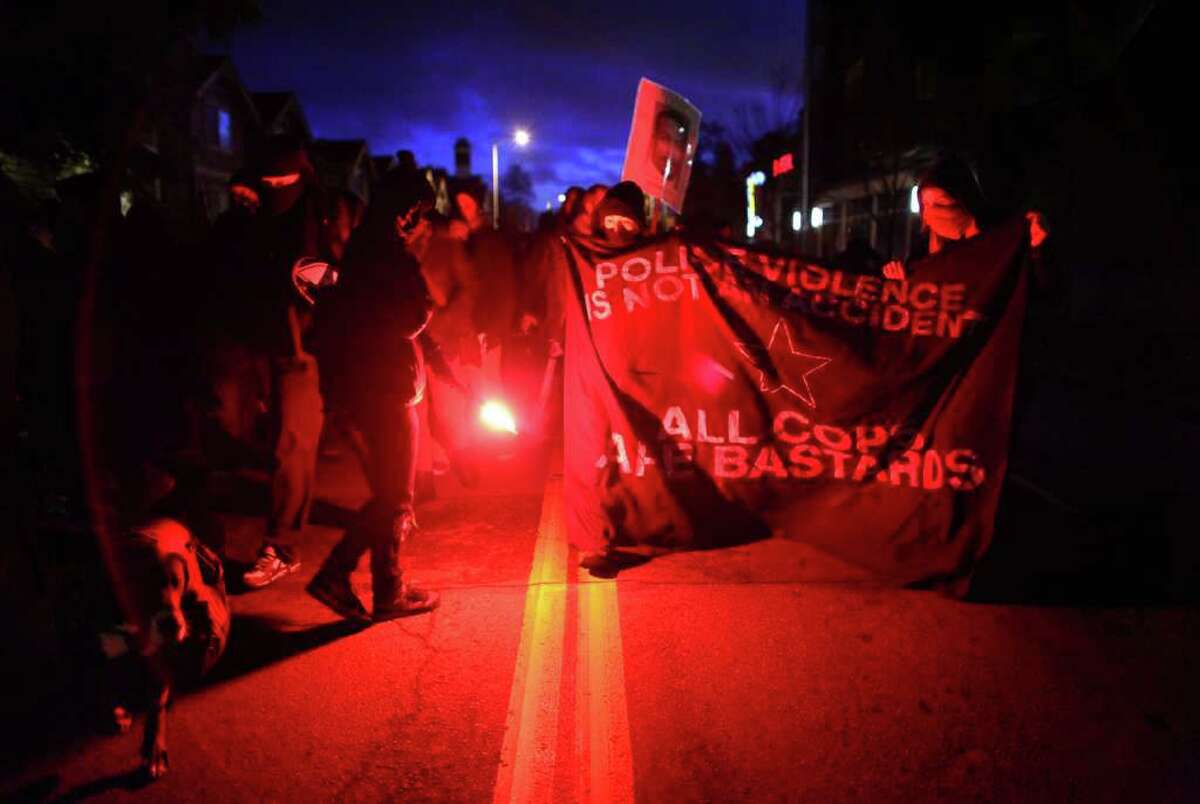 Protesters, many wearing masks, march on 23rd Avenue to the Seattle Police Department's East Precinct while carrying road flares on Saturday, January 14, 2012. Participants in the rally were demanding that Chief John Diaz step down. About 50 people participated in the march.