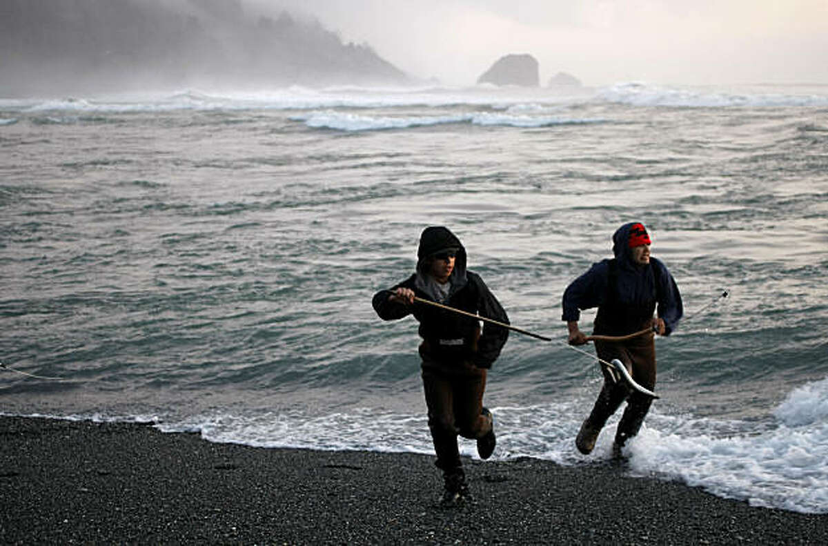 Yurok tribe members, Ira Thompson, left, hooks a Lamprey Eel from the waters of the Klamath River where it meets the PAcific Ocean, Desmond Oliver runs along side as they exit the waters. Photo By Michael Macor/San Francisco Chronicle Photographed in, Klamath, Ca, on 2/11/08