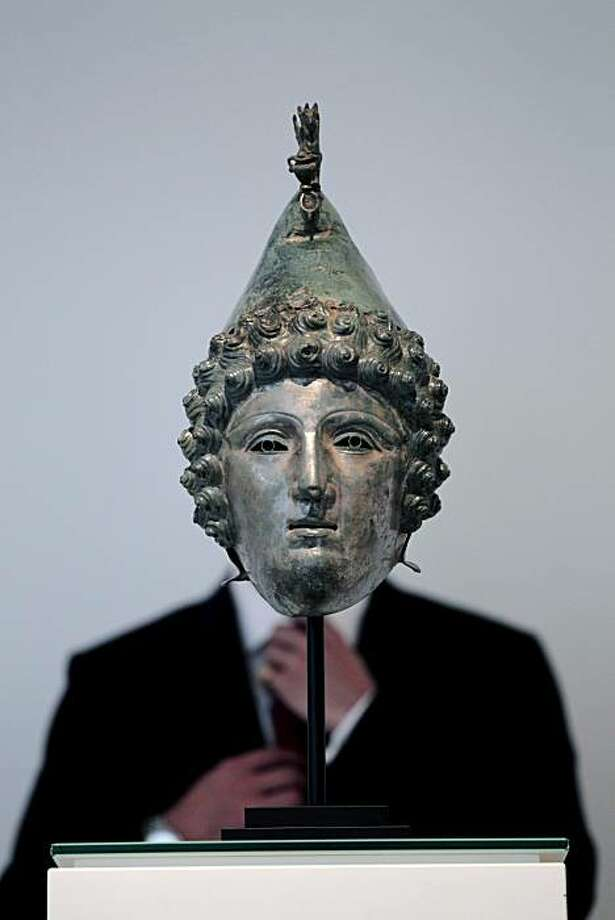 A Christie's employee poses for photographs behind a Roman bronze helmet found with the use of a metal detector, at the auction house's offices in London, Monday, Sept. 13, 2010. The helmet is topped with a griffin. The face mask features perfectly archedeyebrows and an ancient gaze, framed by curls. And it is up for auction. Considered an extraordinary example of Roman metalwork, the mask was discovered in a field in northwestern England by a treasure-hunter armed with a metal detector. It is to be offered at auction Oct. 7 by Christie's, with a guide price of 200,000 to 300,000 pounds, euro 240, 000 to 360, 000 ($242,000 to 363,000). Photo: Matt Dunham, AP