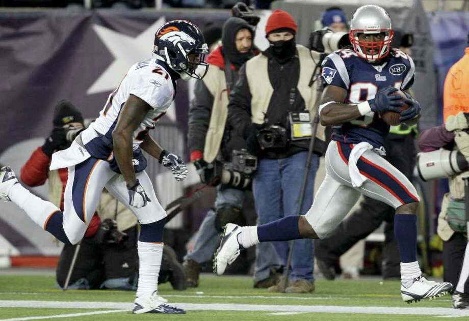 Denver Broncos cornerback Andre' Goodman (21) tries to stop New England Patriots wide receiver Deion Branch (84) as he scores on a 61-yard touchdown during the first half of an NFL divisional playoff football game Saturday, Jan. 14, 2012, in Foxborough, Mass. Photo: AP