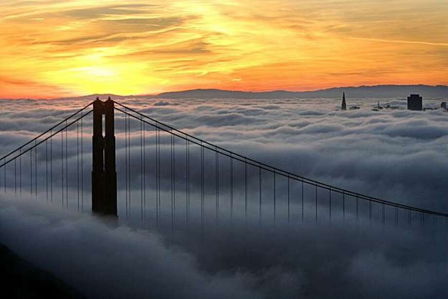 Just the tops of the tallest building of the San Francisco skyline was visual just before sunrise as viewed from the Marin headlands looking through the Golden Gate Bridge. Photo: Frederic Larson, The Chronicle