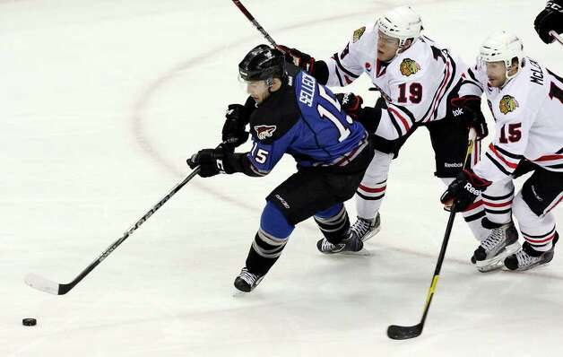 The Rampage's Eric Selleck chases after the puck ahead of the IceHogs' Jeremy Morin and Brett McLean during first period action Saturday, Jan. 14, 2012 at the AT&T Center. Photo: Eaornelas@express-news.net, EDWARD A. ORNELAS / SAN ANTONIO EXPRESS-NEWS (NFS)