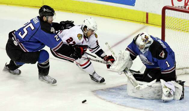 The Rampage's Dov Grumet-Morris stops a shot on goal by the IceHogs' Brandon Pirri as the Rampage's Colby Robak moves in on the play during first period action Saturday, Jan. 14, 2012 at the AT&T Center. Photo: Eaornelas@express-news.net, EDWARD A. ORNELAS / SAN ANTONIO EXPRESS-NEWS (NFS)