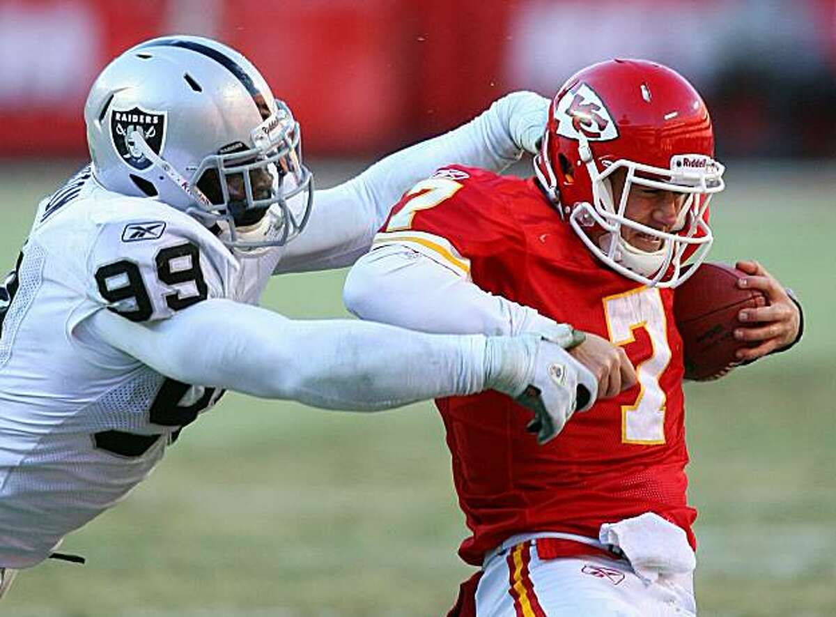 KANSAS CITY, MO - JANUARY 02: Quarterback Matt Cassel #7 of the Kansas City Chiefs is sacked by defensive end Lamarr Houston #99 of the Oakland Raiders in a game at Arrowhead Stadium on January 2, 2011 in Kansas City, Missouri. The Raiders won 31-10