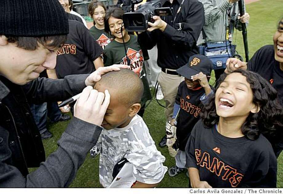 Giants pitcher, Tim Lincecum, left, signs C.J. Carter's (8) forehead as Nicole Ruiz, 8, laughs. Cy Young award winner Tim Lincecum spent the afternoon signing autographs for the San Bruno/Bayview Hunters' Point Junior Giants league at AT&T Park in San Francisco, Calif., on Tuesday, November 11, 2008, and then appeared at news conference after the announcement that he's been named the top pitcher in the National League. Photo: Carlos Avila Gonzalez, The Chronicle