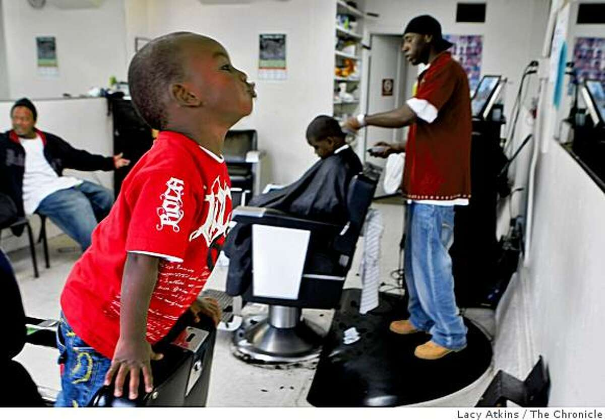 Terreon Hunt, 2 years old, makes faces in the mirror while Terrance Powell cuts Ahmaond Balls' hair on Wednesday Nov. 12, 2008, at The Shop in the Visiticion Valley district in San Francisco, Calif.
