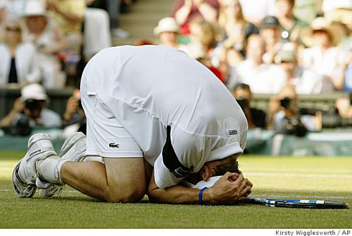 Andy Roddick of U.S.falls to the ground after defeating Britain's Andy Murray, in their men's singles semifinal on the Centre Court at Wimbledon, Friday, July 3, 2009. (AP Photo/Kirsty Wigglesworth)