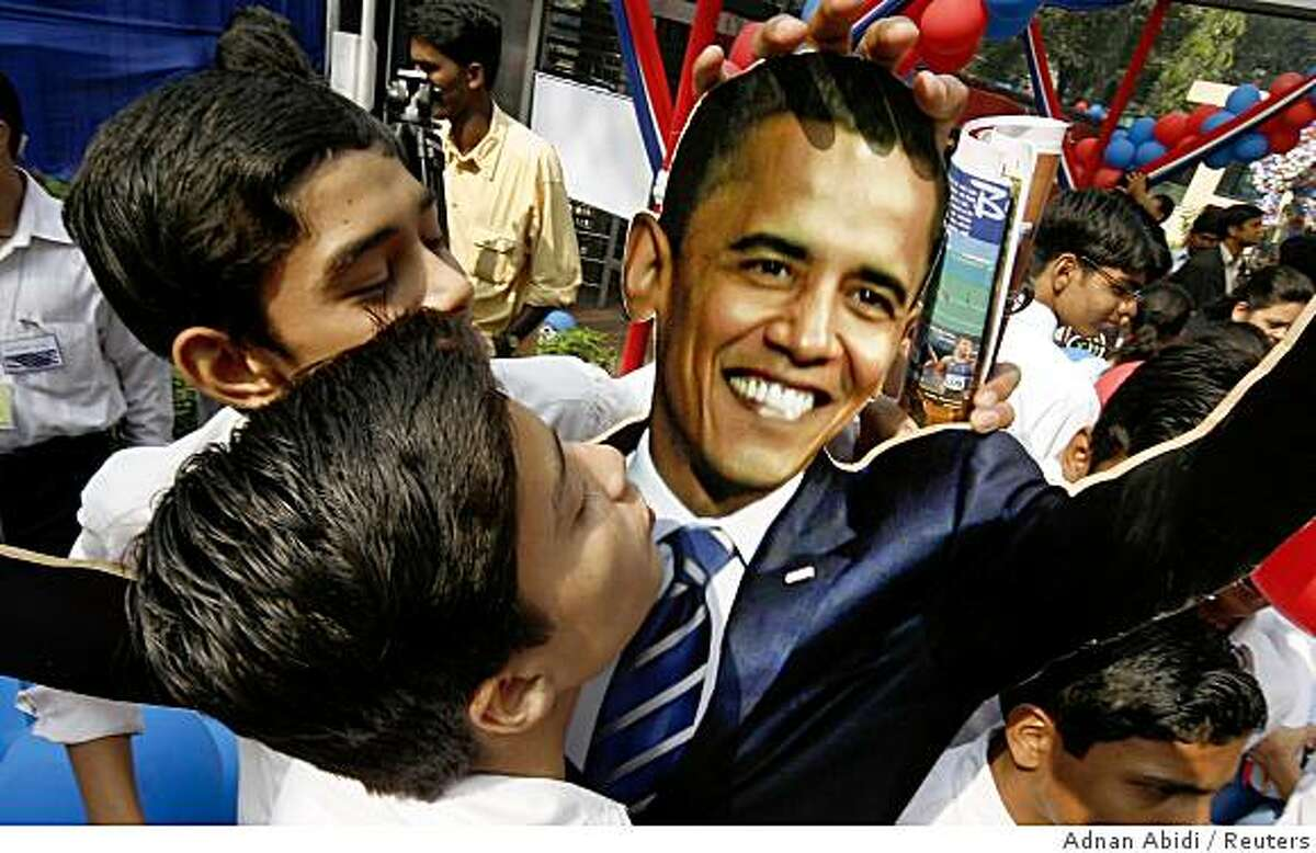 Students reach out to kiss a cutout of U.S. President-elect Senator Barack Obama (D-IL) at the American Centre in New Delhi November 5, 2008. India hailed the election of Obama as the next U.S. president on Wednesday, saying his