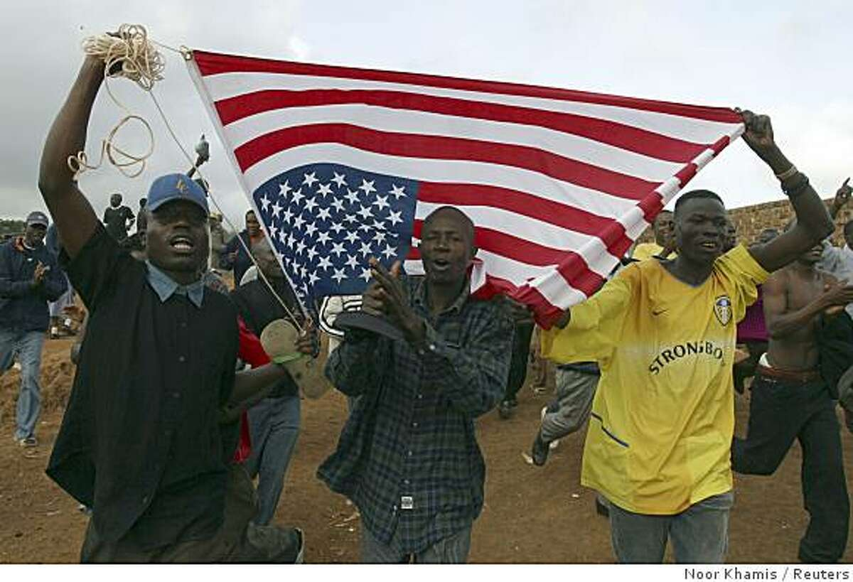 People carry an U.S. flag as they celebrate U.S. President-elect Senator Barack Obama's (D-IL) historic White House victory in Nairobi's Kibera slum November 5, 2008. Kenyans in Obama's ancestral homeland sang and danced with joy on Wednesday as the Illinois senator they see as one of their own became the first black U.S. president.