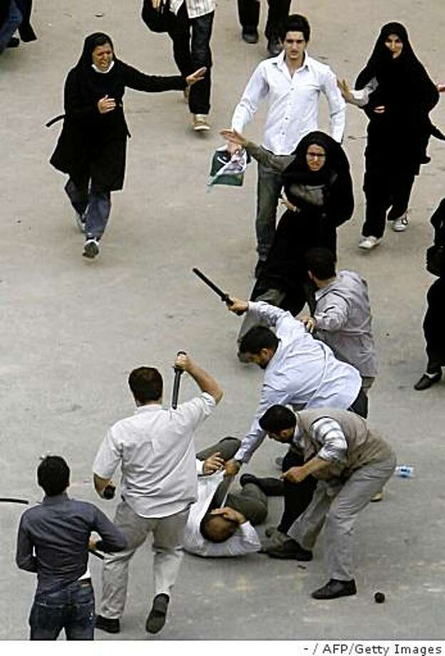 Iranian plain clothes policemen beat a demonstrator with batons during a protest against the election results in Tehran on June 14, 2009. Photo: -, AFP/Getty Images