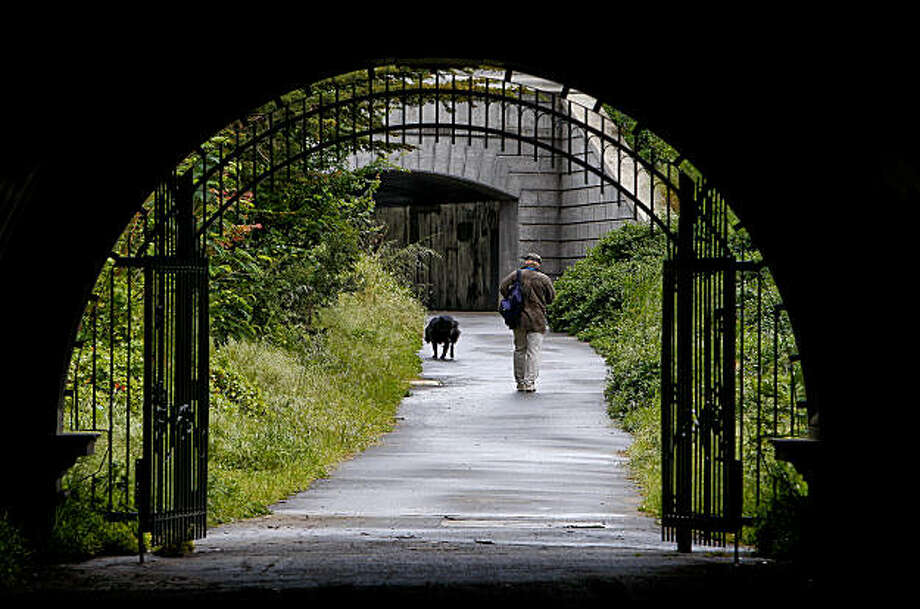 During a break in the rains, Richard Lindstrom of San Francisco walks his dog, Justine, through a tunnel that goes under John F. Kennedy Drive in Golden Gate Park, on Tuesday Apr. 27, 2010, in San Francisco, Calif. Photo: Michael Macor, The Chronicle