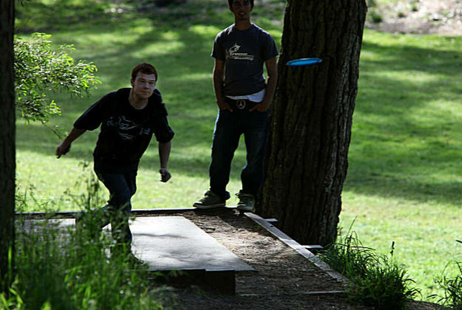 Eric Dettmann (left) throws to disc golf basket #16 at the disc golf course in Golden Gate Park, San Francisco, Calif., on Monday, May 24, 2010. Travis Rybiski (right), from Millbrae, waits his turn. Photo: Liz Hafalia, The Chronicle
