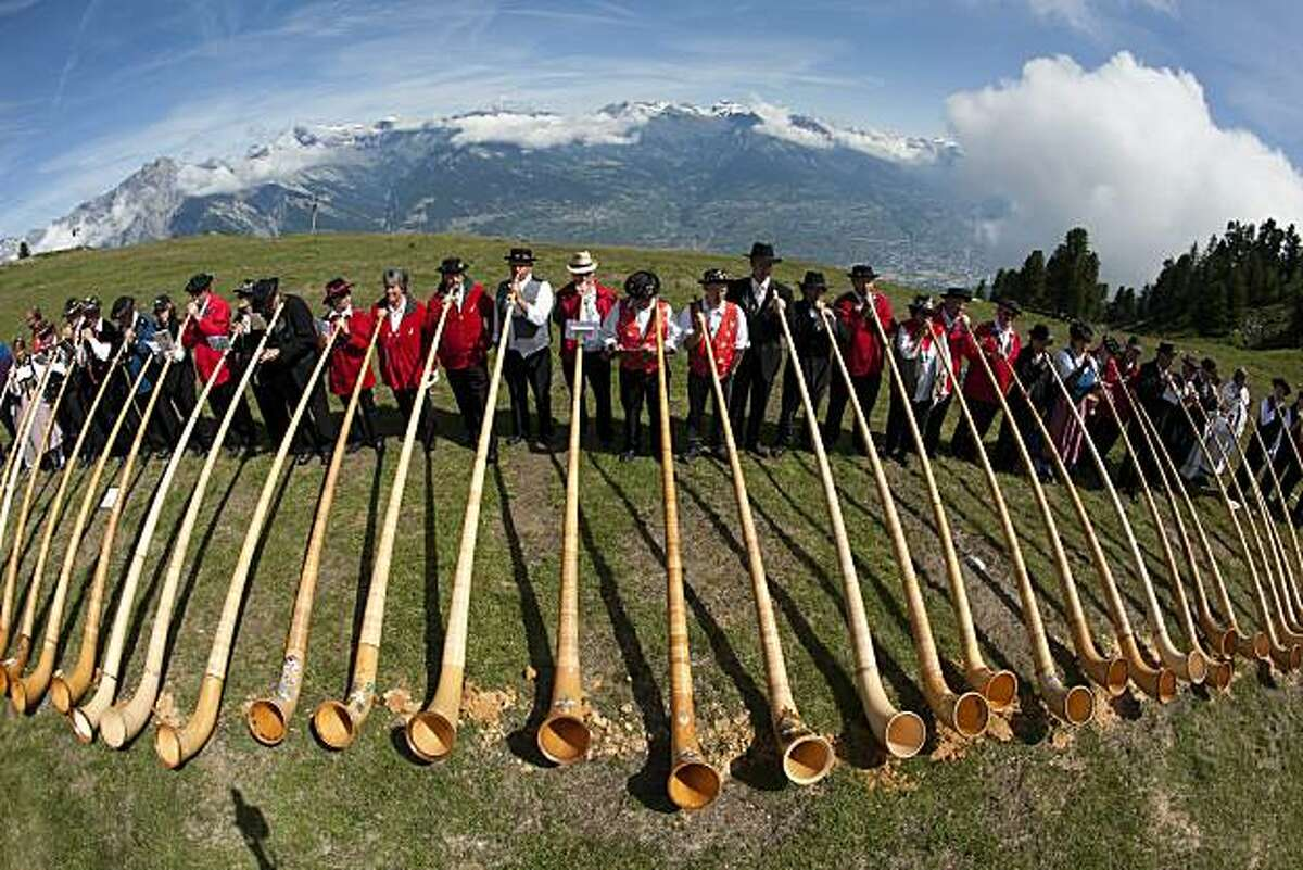 Some of 160 alphorn players perform during the 9th international alphorn festival in Nendaz, south western Switzerland, Sunday, July 25, 2010.
