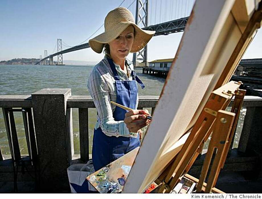Painter Heather Capen finishes a painting of the Oakland San Francisco Bay Bridge and San Francisco Bay from the Embarcadero near Pier 22 1/2 in San Francisco, Calif., on Wednesday, Oct. 15, 2008. Capen and other Mission district artists will host open studios this weekend. Photo: Kim Komenich, The Chronicle