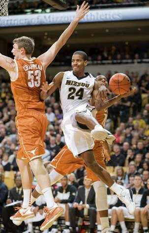 Missouri's Kim English, center, passes the all under the basket around Texas' Clint Chapman, left, and Texas' Jonathan Holmes, right, during the second half of an NCAA college basketball game Saturday, Jan. 14, 2012, in Columbia, Mo. Missouri won the game 84-73. Photo: Associated Press, L.G. PATTERSON