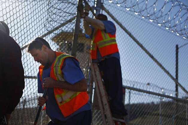 Jeff Jones and Woodie Pruitt, inmates who work at the mechanical maintenance shop, work on a gate installation outside the new care facility at California Medical Facility in Vacaville on Friday, January 13, 2012 in Vacaville, Calif. Photo: Lea Suzuki, The Chronicle
