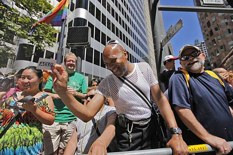 Willie Colbert, center, smiles as he gets a package of sunscreen, thinking it was lubricant, from someone marching in the 40th annual Gay Pride Parade on Sunday in San Francisco. Photo: Lacy Atkins, The Chronicle