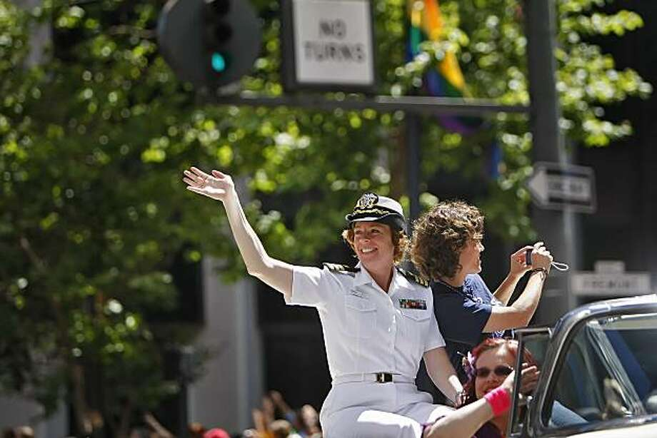 Navy Reserve Commander Zoe Dunning and her partner, Pam Grey, wave and photograph the thousands watching the 40th annual Gay Pride Parade on Sunday in San Francisco. Zoe made history when she came out as a lesbian and won her discharge case against the military. Photo: Lacy Atkins, The Chronicle